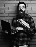 拿着膝上型计算机和工艺纸的有胡子的残酷白种人行家 库存图片
