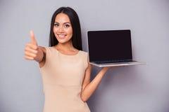 拿着膝上型计算机和显示赞许的妇女 免版税库存图片