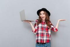 拿着膝上型计算机和copyspace在她的棕榈的少年女孩 库存图片
