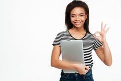 拿着膝上型计算机的一个愉快的美国黑人的青少年的女孩的画象 免版税图库摄影