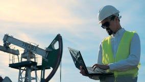 拿着膝上型计算机的一名男性工作者的运作的过程在一个作用的气体井架旁边 能量,石油,气体,燃料抽的船具 股票录像