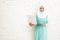 拿着膝上型计算机的亚洲少妇佩带的hijab 库存图片