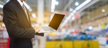 拿着膝上型计算机的商人手在迷离超级市场 库存照片