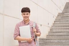 拿着膝上型计算机的学院亚裔男学生在校园里 图库摄影