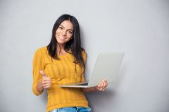 拿着膝上型计算机的微笑的美丽的妇女 图库摄影