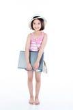拿着膝上型计算机的愉快的亚裔女孩 免版税库存图片