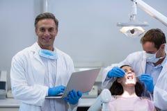 拿着膝上型计算机的牙医画象在牙齿诊所 免版税库存图片