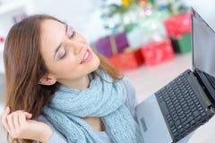 拿着膝上型计算机的特写镜头美丽的妇女在圣诞节 图库摄影