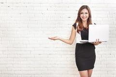 拿着膝上型计算机的美丽的妇女,当提出拷贝空间时 免版税库存照片