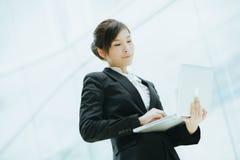 拿着膝上型计算机的年轻亚裔女实业家 库存图片