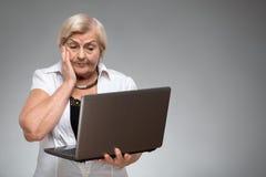 拿着膝上型计算机的年长妇女 库存照片