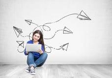 拿着膝上型计算机,纸飞机的牛仔裤的十几岁的女孩 图库摄影