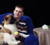 拿着膝部小狗的白男子气概的人 库存照片