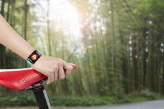拿着自行车位子佩带的健康传感器巧妙的手表的妇女手 免版税库存照片