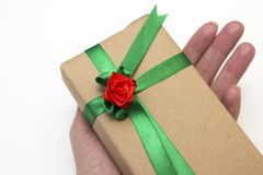 拿着节日礼物的女孩的手被包装在纸和栓与与一朵红色玫瑰花的一条绿色丝带 库存照片