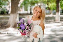 拿着花和玩具的俏丽的构成的微笑的妇女 库存照片