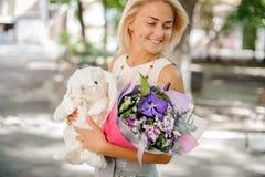 拿着花和玩具的构成的微笑的妇女 库存图片