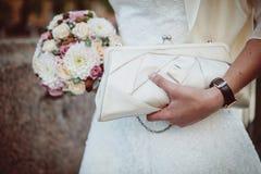 拿着花束和提包的新娘 免版税库存照片