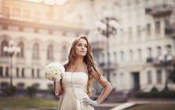 拿着花束的一件白色礼服的可爱的女孩 库存图片