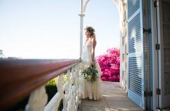 拿着花束的俏丽的新娘,当站立在阳台上时 免版税库存图片