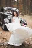 拿着花束的典雅的白色礼服的美丽的新娘摆在公园 免版税库存图片