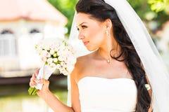拿着花束的婚礼礼服的年轻新娘 库存图片