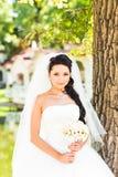 拿着花束的婚礼礼服的年轻新娘 免版税库存图片