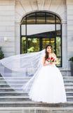 拿着花束的婚礼礼服的年轻新娘 免版税库存照片