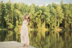 拿着花束的庄重装束的华美的新娘摆在森林和湖附近 免版税库存图片