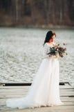 拿着花束的庄重装束的华美的深色的新娘摆在森林和湖附近 库存照片