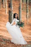 拿着花束的庄重装束的华美的深色的新娘摆在森林和湖附近 库存图片