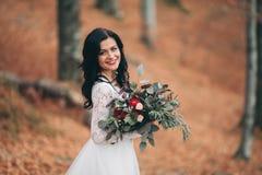 拿着花束的庄重装束的华美的深色的新娘摆在森林和湖附近 免版税库存照片
