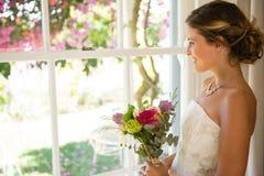 拿着花束的微笑的美丽的新娘侧视图,当看通过窗口时 库存照片