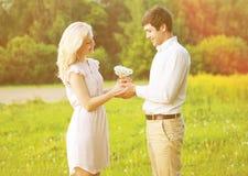 拿着花束的愉快的微笑的夫妇 免版税库存照片