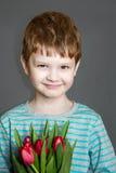 拿着花束的愉快的男孩 免版税库存照片