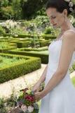 拿着花束的新娘在规则式园林里 免版税库存照片