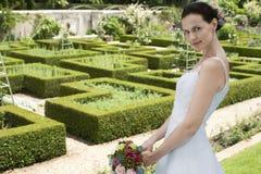 拿着花束的新娘在规则式园林里 免版税图库摄影