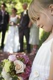 拿着花束的逗人喜爱的矮小的女花童在庭院里 库存图片