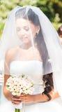 拿着花束的面纱的严肃的年轻新娘 库存图片