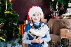 拿着花样滑冰的圣诞老人帽子的孩子 库存照片