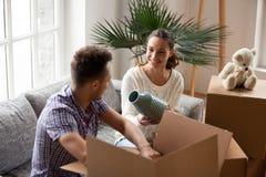 拿着花瓶帮助的人包装盒的妇女在移动的天 免版税图库摄影
