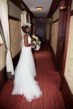 拿着花的一个美丽的非裔美国人的新娘的侧视图 免版税库存图片