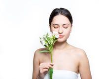拿着花的俏丽的女孩在面孔附近和吸入它的fragr 免版税库存照片