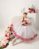 拿着花的可爱的芭蕾舞女演员 免版税库存照片
