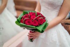 拿着花的她的红色婚礼花束新娘 免版税库存图片