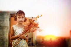 拿着花的小小女孩梦想的画象  免版税库存图片