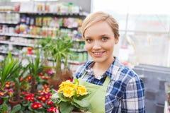 拿着花的愉快的妇女自温室 免版税图库摄影