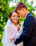 拿着花的新娘和新郎室外 免版税库存照片