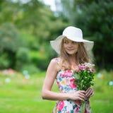 拿着花的白色帽子的女孩 免版税图库摄影
