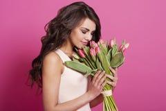 拿着花的美丽的妇女 库存图片